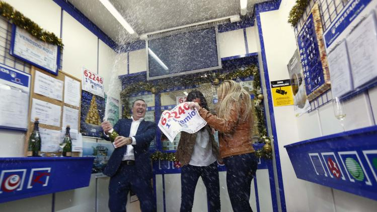 "Lottery shop employees spray champagne as they show a poster of the winning number to the first prize of ""El Gordo"" at a lottery shop where the number was sold in Sanlucar la Mayor"