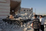 Syrians look at a destroyed army tank parked outside the Azaz mosque, north of the restive city of Aleppo, on August 2. Shells have rained down on rebel positions in Aleppo ahead of a UN vote to deplore both the Syrian regime's use of heavy arms and world powers for failing to agree on steps to end the conflict