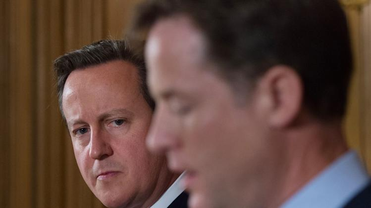 Britain's Prime Minister David Cameron listens to Deputy Prime Minister Nick Clegg speak at a joint news conference at 10 Downing Street in central London