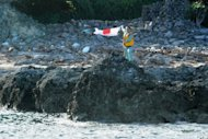 A Japanese activist waves the country&#39;s flag after landing on the disputed islands in the Eash China Sea on August 19. About a dozen Japanese nationalists raised their country&#39;s flag on Uotsurijima island, prompting protests in cities across China