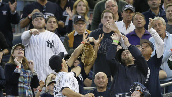 New York Yankees' Mark Teixeira reaches for a foul ball hit by Detroit Tigers's Delmon Young in the seventh inning of Game 2 of the American League championship series Sunday, Oct. 14, 2012, in New York. (AP Photo/Matt Slocum)