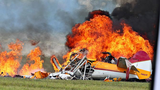 Flames erupt from a plane after a stunt plane crashed while performing with a wing walker at the Vectren Air Show, Saturday, June 22, 2013, in Dayton, Ohio. The crash killed the pilot and the wing walker instantly, authorities said. (AP Photo/Thanh V Tran)