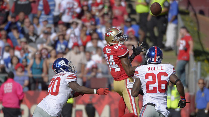 San Francisco 49ers wide receiver Randy Moss (84) catches a pass over New York Giants cornerback Prince Amukamara (20) and free safety Antrel Rolle (26) during the third quarter of an NFL football game in San Francisco, Sunday, Oct. 14, 2012. (AP Photo/Mark J. Terrill)