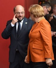 German Chancellor Angela Merkel (R) and European Parliament President Martin Schulz arrive to take their positions for a group photo at a EU summit in Brussels. EU leaders Thursday vowed to set up a banking union during the course of 2013 after a Franco-German spat held up agreement on exactly when this vital crisis-fighting tool might come into force