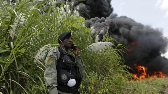A police officer stands guard as confiscated drugs are incinerated in Panama City