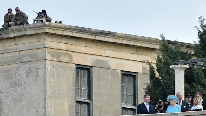 Snipers stand on a roof as Queen Elizabeth II and her husband Prince Philip visit the Heritage Malta centre on the sidelines of the Commonwealth Heads of Government Meeting (CHOGM) in Malta on November 28, 2015