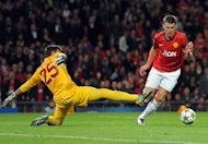 Manchester United's midfielder Michael Carrick (R) beats Galatasaray's goalkeeper Fernando Muslera to score during an UEFA Champions League Group H football match at Old Trafford in Manchester. Manchester United won 1-0