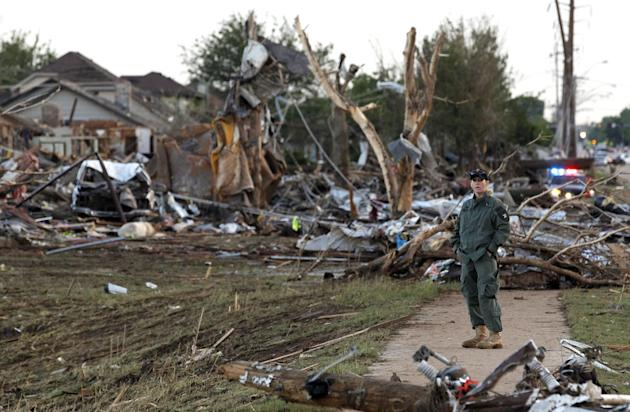 A member of a security team helps guard an area of rubble from a destroyed residential neighborhood, one day after a tornado moved through Moore, Okla., Tuesday, May 21, 2013. The huge tornado roared
