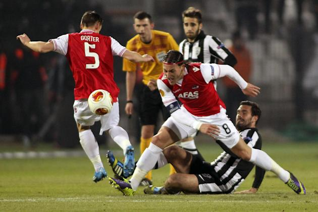 Paoks' Alexandros Tziolis, centre on ground,  fights for the ball with AZ Alkmaar's Nemanja Gudelj, during their Champions Europa League Group M soccer match at the Toumba stadium in the north