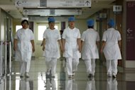 Illustration: a group of nurses walks along a corridor at a hospital in Beijing on July 29, 2013
