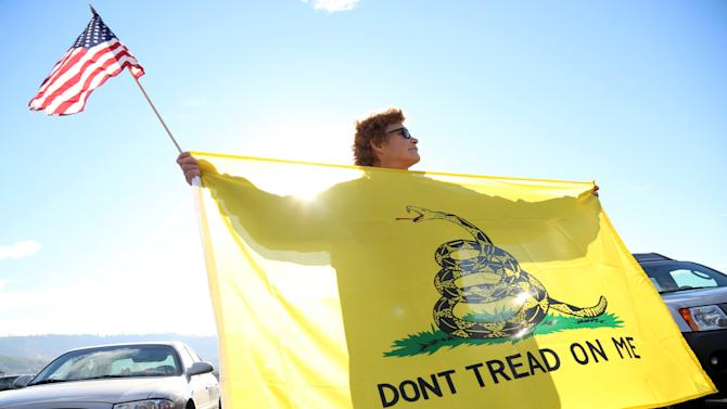 Leslie Corp holds up an American flag and the Gadsden flag while waiting outside of Roseburg Municipal Airport for President Barack Obama's arrival in Roseburg, Ore., Friday, Oct. 9, 2015. Gun-rights activists say they plan to protest when Obama visits here Friday to meet with families of victims of last week's college shooting rampage. They are angry about Obama's call for more gun restrictions after the killing of eight students and a teacher. (AP Photo/Ryan Kang)