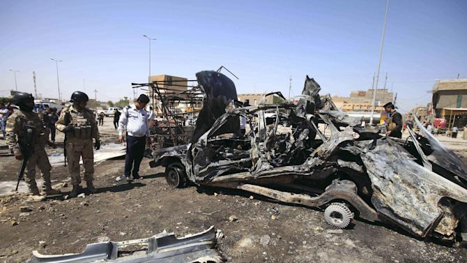 Iraqi security forces inspect the site of a car bomb attack in Basra, 340 miles (550 kilometers) southeast of Baghdad, Iraq, Sunday, Sept. 15, 2013. A new wave of insurgent attacks, mostly car bombs targeting Shiite-dominated cities in central and southern Iraq, killed and wounded scores of people, officials said. (AP Photo/ Nabil al-Jurani)