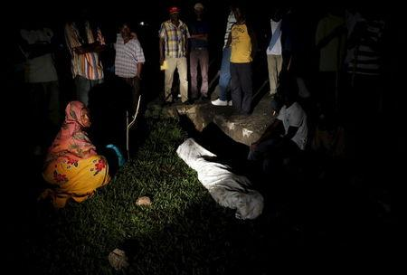Relatives and friends gather around the covered body of Zedi Feruzi, the head of opposition party UPD, in Bujumbura, Burundi