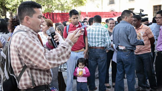"""In this Jan. 17, 2013 photo, political activist Frank Mejia, better known as """"Commander Maya,"""" reads a manifest in support of teachers protesting to demand months of unpaid salaries outside Congress in Tegucigalpa, Honduras.  Teachers have been demonstrating almost every day because they haven't been paid in six months, while doctors complain about the shortage of essential medicines, gauze, needles and latex gloves. This Central American country has been on the brink of bankruptcy for months, as lawmakers put off passing a government budget necessary to pay for basic government services.  (AP Photo/Alberto Arce)"""