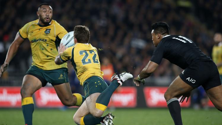 Foley of Australia's Wallabies dives to catch the ball as he is watched by Savea of New Zealand's All Blacks and teammate Wycliff Palu during their Bledisloe Cup rugby championship match in Auckland