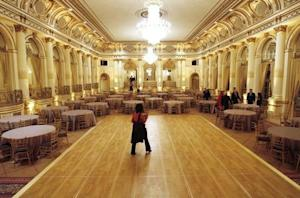 """A journalist walks across the dance floor in the """"Grand Ballroom"""" of """"The Plaza"""" hotel as it re-opens in New York"""