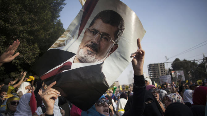 An Egyptian woman holds a portrait of ousted Egyptian President Mohammed Morsi during a protest in Nasr City in Cairo, Egypt, Friday, Nov. 1, 2013. The trial of Morsi opens Monday, presenting serious challenges for the military-backed authorities. Days before the trial, the location of where he will be tried has not been announced for security reasons. His supporters threaten massive protests that may disrupt the proceedings. And in his anticipated first public appearance after four months in secret military detention, Morsi could turn his trial on charges of inciting murder into a platform for indicting the coup, giving more vigor to the opposition.(AP Photo/Manu Brabo)