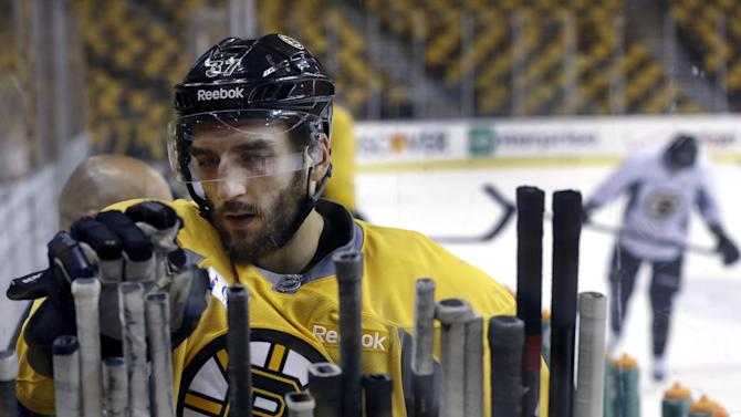 Boston Bruins center Patrice Bergeron grabs a stick as he leaves the ice after practice at TD Garden in Boston, Monday, June 10, 2013. The Bruins are preparing to face the Chicago Blackhawks in the NHL hockey Stanley Cup finals with Game 1 scheduled for Wednesday in Chicago. (AP Photo/Elise Amendola)