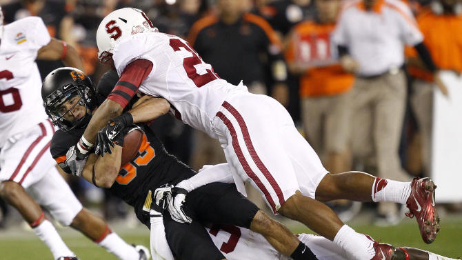 Oklahoma State wide receiver Colton Chelf, left, is tackled by Stanford safety Delano Howell, right, during the first half of the Fiesta Bowl NCAA college football game Monday, Jan. 2, 2012, in Glendale, Ariz. (AP Photo/Matt York)