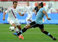 Roman Shirokov (L) of Russia clashes for the ball with Alvaro Pereira (R) of Uruguay during their friendly match in Moscow. Russia began their warm-up for Euro 2012 with a 1-1 draw against 2010 World Cup semi-finalists Uruguay