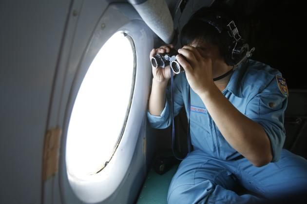Military officer Dang Xuan Hung looks out a window of a Vietnam Air Force aircraft AN-26 during a mission to find the missing Malaysia Airlines flight MH370 off Con Dao island