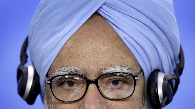The Prime Minister of India, Manmohan Singh, wears a headphone as he attends a joint press conference with German Chancellor Angela Merkel, unseen, as part of a meeting at the chancellery in Berlin, Germany, Thursday, April 11, 2013. (AP Photo/Michael Sohn)