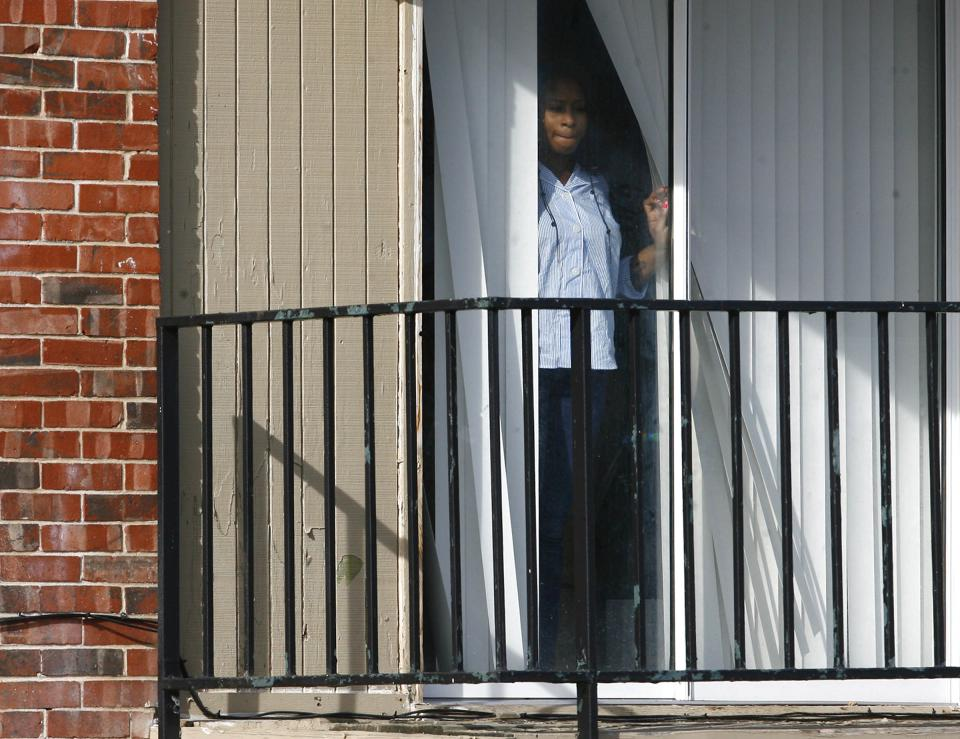 A woman watches as police investigate  a quadruple homicide at Tulsa's Fairmont Terrace apartment complex on Monday, January 7, 2013. Four women were found shot to death inside an apartment, where a 4-year-old boy was also found unharmed.  (AP Photo/Tulsa World, Matt Barnard )   TV OUT; TULSA OUT