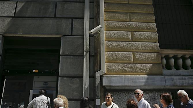 People line up at an ATM outside a closed National Bank branch, after the Greek government imposed capital controls at the country's banks in Athens