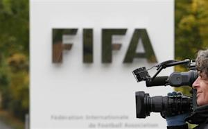 A cameraman films in front of the main entrance of the Home of FIFA in Zurich