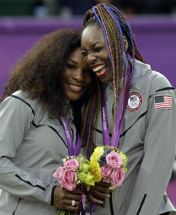 Serena Williams, left, and Venus Williams of the United States laugh together on the podium after receiving their gold medals in women's doubles at the All England Lawn Tennis Club in Wimbledon, Londo