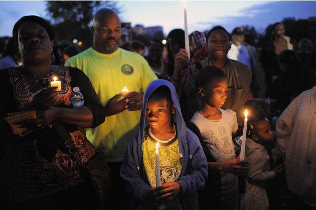 A boy wears hooded sweatshirt, as he joins a candlelight vigil at exact moment when Martin was shot a year ago in Sanford