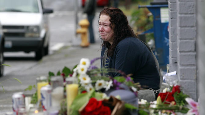Stacy Davis cries as she sits near a growing memorial at the scene of where a gunman killed four people and severely wounded another in a cafe a day earlier, Thursday, May 31, 2012, in Seattle. Police say he later killed a woman during a carjacking before shooting himself. As officers closed in during a widespread manhunt on Wednesday, the suspect put a gun to his head, pulled the trigger and later died at a hospital. (AP Photo/Elaine Thompson)