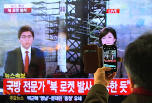 South Korean man uses his smartphone to take a television screen reporting a news about North Korea's rocket launch at Seoul Railway Station in Seoul, South Korea, Wednesday, Dec. 12, 2012. North Kore