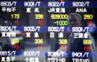 A passer-by is reflected on the electronic stock board of a securities firm in Tokyo, Japan, Wednesday, June 29, 2011. The Nikkei Stock Average rose 148.28 points, or 1.54 percent, from Tuesday to 9,797.26. Signs that a global economic slowdown may be less serious than previously thought and a recovery in manufacturing in post-quake Japan sent Asian stock markets higher Wednesday. (AP Photo/Shizuo Kambayashi)