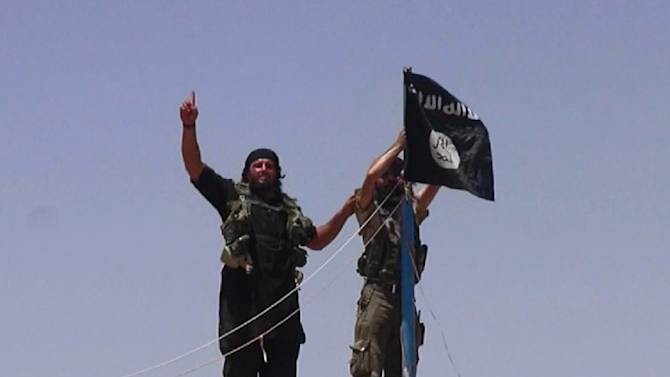 An image made available by the jihadist Twitter account Al-Baraka news allegedly shows militants of the Islamic State jihadists hanging the Islamic Jihad flag on a pole at the top of an ancient military fort in Iraq on June 11, 2014