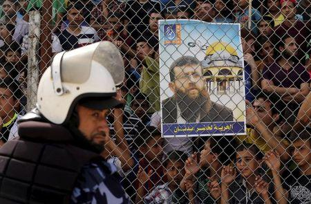 Palestinian policeman loyal to Hamas stands guard as spectators stand behind a fence and hold a poster depicting Palestinian prisoner Adnan as they watch the Gaza Strip Cup final soccer match in Gaza City