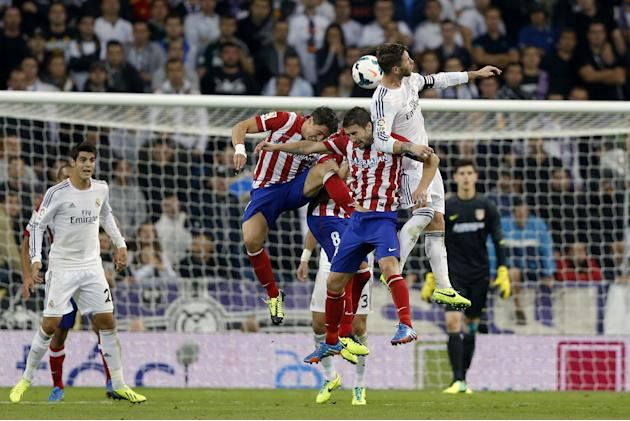 Real Madrid's Sergio Ramos, right, jumps for the ball with Atletico de Madrid's Gabi Fernandez, second from right, Raul Garcia (8), center, and Cristian Rodriguez from Uruguay, third from right, as Re