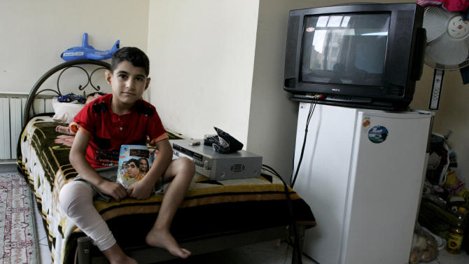 In this Sunday, Aug. 5, 2012 photo, Iranian Milad Rostami, 8, who is suffering from hemophilia, currently recovering from knee surgery, sits on his bed at Iran's Hemophilia Association center, in Tehran, Iran. While medicine and humanitarian supplies are not blocked by the economic embargoes on Iran over its nuclear program, the pressures are clearly evident in nearly every level of Iranian health care. It's a sign of the domino effect of sanctions on everyday life. (AP Photo/Vahid Salemi)