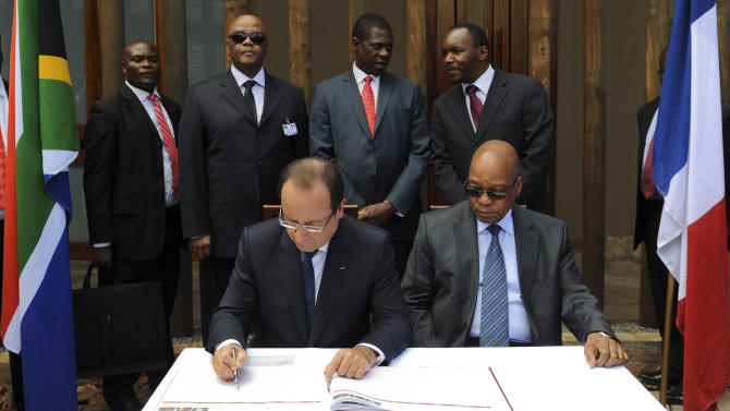 French president Francois Hollande, left, accompanied by South African president Jacob Zuma, right, signs a visitors book during a visit to Freedom Park, Pretoria, South Africa, Monday, Oct. 14, 2013. Hollande, who is on a two-day state visit to the country, praised South Africa for its efforts to stabilize conflict-prone parts of Africa. (AP Photo)
