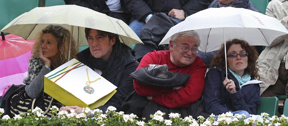 Spectators watch from under their umbrellas as Victoria Azarenka of Belarus plays against Germany's Annika Beck in their second round match at the French Open tennis tournament, at Roland Garros stadium in Paris, Thursday, May 30, 2013. (AP Photo/Michel Euler)