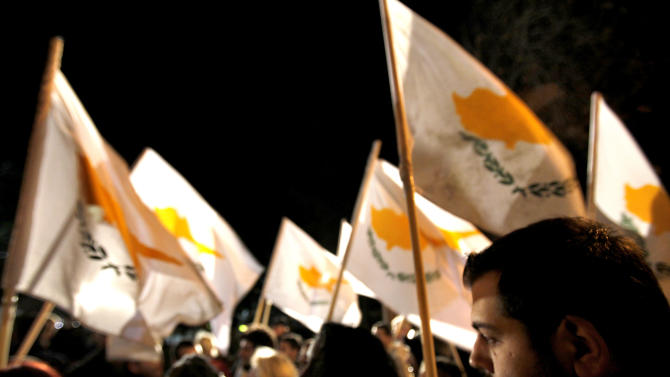 "Protestors hold Cyprus' flags during a rally outside the parliament in capital Nicosia, Cyprus, Friday, March 22, 2013. Cypriot authorities were putting the final touches Friday to a plan they hope will convince international lenders to provide the money the country urgently needed to avoid bankruptcy within days. ""The next few hours will determine the future of this country,"" said government spokesman Christos Stylianides. (AP Photo/Petros Karadjias)"