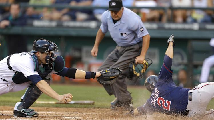 Seattle Mariners catcher Mike Zunino, left, can't tag Minnesota Twins' Brian Dozier (2) as he slides home to score a run on a sacrifice fly hit by Twins Kurt Suzuki in the third inning of a baseball game, Thursday July 10, 2014, in Seattle. (AP Photo/Ted S. Warren)