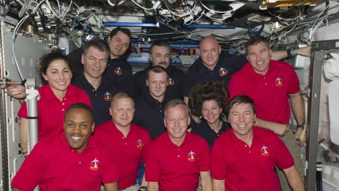 In this March 3, 2011 photo provided by NASA, inside the U.S. lab Destiny, 12 astronauts and cosmonauts take a break from a very busy week aboard the International Space Station to pose for a joint STS-133/Expedition 26 group portrait. The STS-133 crew members, all attired in red shirts, from left, are NASA astronauts Nicole Stott, Alvin Drew, Eric Boe, Steve Lindsay, Michael Barratt and Steve Bowen. The dark blue-attired Expedition 26 crew members, from left, are European Space Agency astronaut Paolo Nespoli, along with Russian cosmonauts Oleg Skripochka, Dmitry Kondratyev, below, and Alexander Y. Kaleri and astronauts Scott Kelly and Cady Coleman, below. Serving the STS-133 and Expedition 26 missions as commanders were Lindsay and Kelly, respectively.  (AP Photo/NASA)