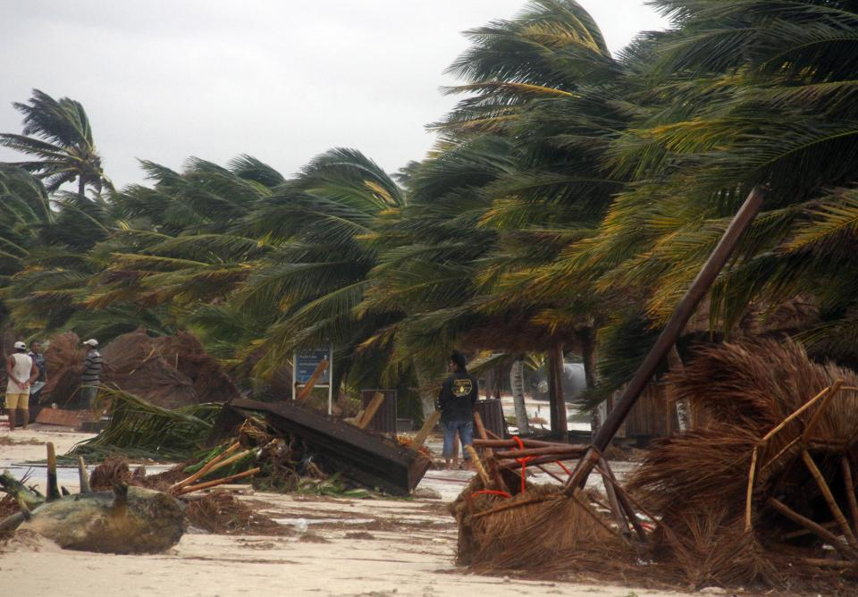 People survey the damage caused by Hurricane Ernesto after it made landfall overnight in Mahahual, near Chetumal, Mexico, Wednesday, Aug. 8, 2012. (AP Photo/Israel Leal)