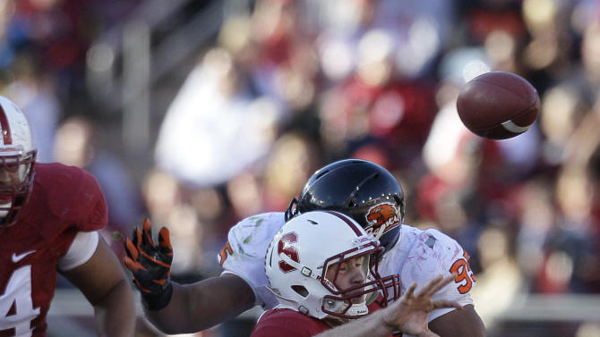 Stanford quarterback Kevin Hogan (8) is hit by Oregon State defensive end Scott Crichton (95) as he throws the ball to running back Stepfan Taylor (33) for a 40-yard touchdown during the third quarter of an NCAA college football game in Stanford, Calif., Saturday, Nov. 10, 2012. (AP Photo/Jeff Chiu)