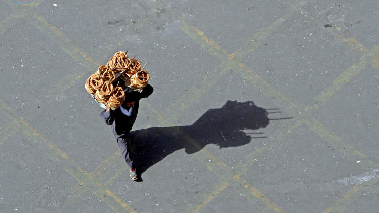 An Egyptian bread vendor walks in Tahrir Square, prior to planned events to mark the second anniversary of former President Hosni Mubarak's resignation, in Cairo, Egypt, Monday, Feb. 11, 2013. Egypt has witnessed a fresh cycle of violence over the past weeks since the second anniversary of the 2011 revolution that deposed longtime autocrat Hosni Mubarak, with clashes across the country having left scores dead and hundreds injured. (AP Photo/Amr Nabil)