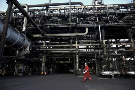 An oilfield worker walks next to pipelines at PDVSA's Jose Antonio Anzoategui industrial complex in the state of Anzoategui