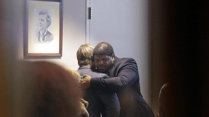Former Dallas Cowboys NFL football player Josh Brent, right, hugs Dallas Cowboys linebacker Sean Lee in court after closing arguments in his intoxication manslaughter trial Tuesday, Jan. 21, 2014, in Waco, Texas. The jury has begun deliberating in Brent's intoxication manslaughter trial after lawyers wrapped up their closing arguments Tuesday morning. Prosecutors accuse the former defensive tackle of drunkenly crashing his Mercedes near Dallas during a night out in December 2012, killing his good friend and teammate, Jerry Brown. (AP Photo/LM Otero)