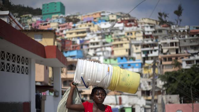 "In this March 21, 2013 photo, a woman carries empty buckets in Jalousie, a cinder block shantytown recently painted in colors in Petionville, Haiti. A $1.4 million effort titled ""Beauty versus Poverty: Jalousie in Colors"" is part of a government project to relocate people from the displacement camps that sprouted up after Haiti's 2010 earthquake.  (AP Photo/Dieu Nalio Chery)"