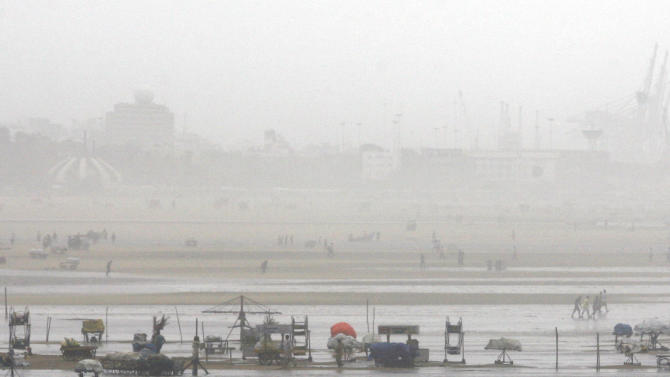 People walk on the Marina beach after the same is flooded with sea water on the Bay of Bengal coast in Chennai, India, Wednesday, Oct. 31, 2012. More than 100,000 people were evacuated from their homes Wednesday as a tropical storm approached southern India from the Bay of Bengal, officials said. Rain was already lashing the region and strong winds uprooted trees in some places. Weather officials said the storm, with wind speeds of up to 100 kilometers (60 miles) per hour, was expected to reach land later Wednesday. (AP Photo/Arun Sankar K)
